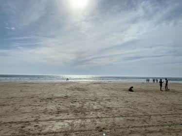 Ein langer Sandstrand, im Hintergrund spiegelt sich die Sonne im Meer.