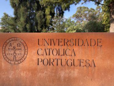 Ein rostfarbenes großes Schild mit dem Logo und dem Schriftzug der Universidade Católica Portuguesa in Lissabon