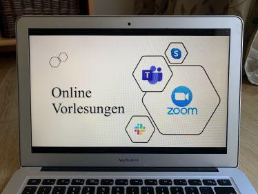 Mein Laptop, auf dessen Bildschirm steht Online Vorlesungen.