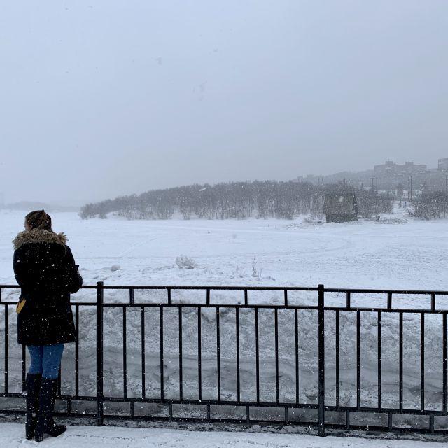 Eine Person steht an einem zugefrorenen See.