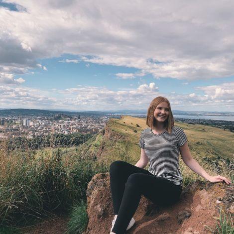 Frau auf Berg sitzend mit Ausblick über die Stadt