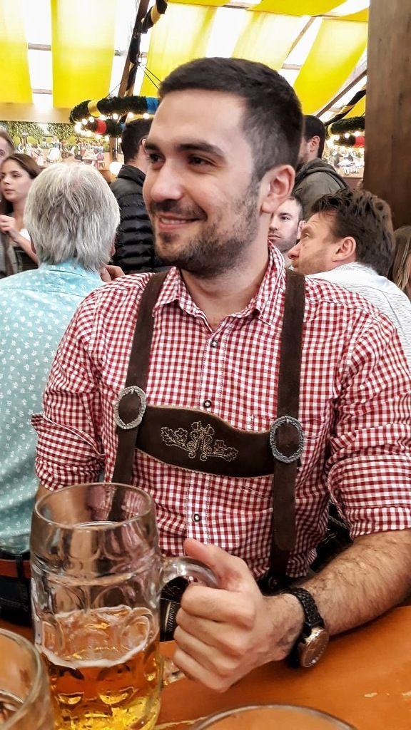 Adrian in Lederhose und rotweißkariertem Hemd, mit Maßkrug, sitzend.