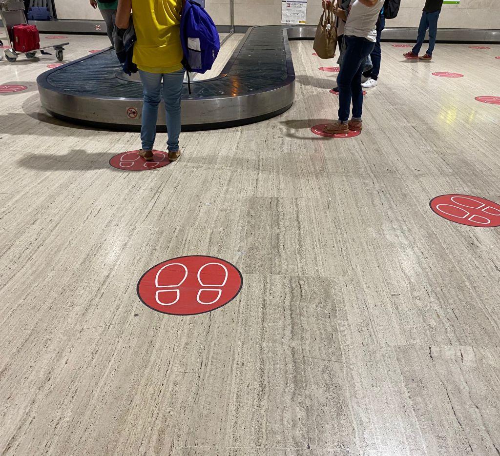 Gepäckannahme-Förderband am Flughafen Sevilla mit roten Markierungen auf dem Boden.