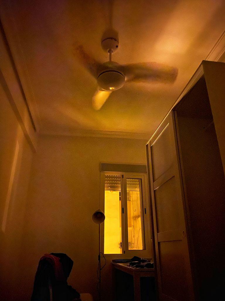 WG-Zimmer bei Nacht. Angeschalteter Deckenventilator und geöffnetes Fenster im Hintergrund.