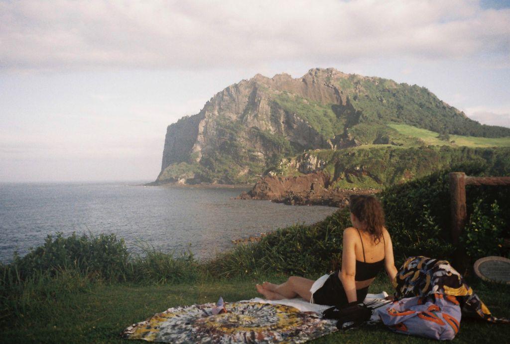 Studentin genießt Ausblick auf das Meer und eine Felsformation