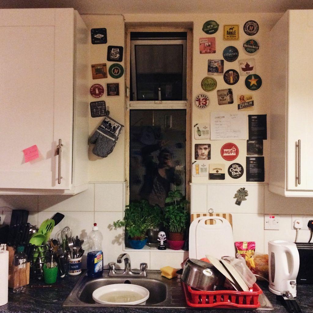 Die Küche einer Wohngemeinschaft. Im Fenster hinter der Spüle spiegelt sich die Person.