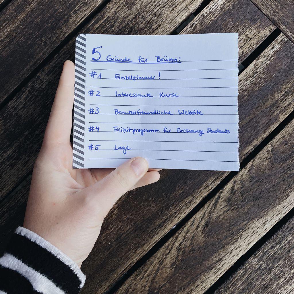 Eine Hand, die einen Zettel hält auf dem 5 Gründe für Brünn aufgelistet sind.