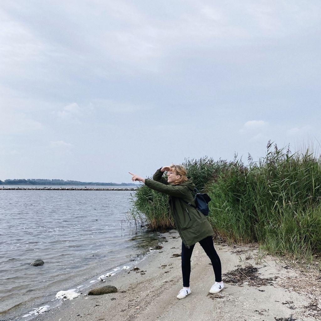 Person, die am Strand steht und aufs Meer zeigt.