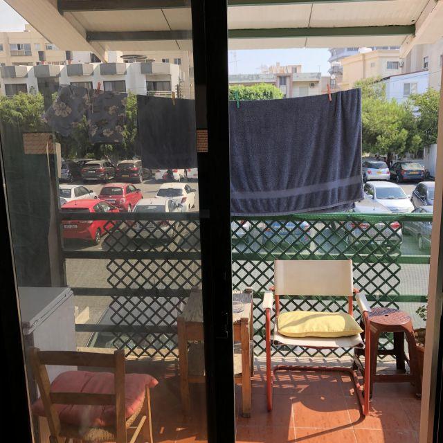 Mein eigener Balkon mit Aussicht auf einen großen Parkplatz.