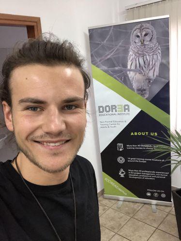 Ein erstes Selfie im Büro vor einem Werbebanner vom Dorea Educational Institute