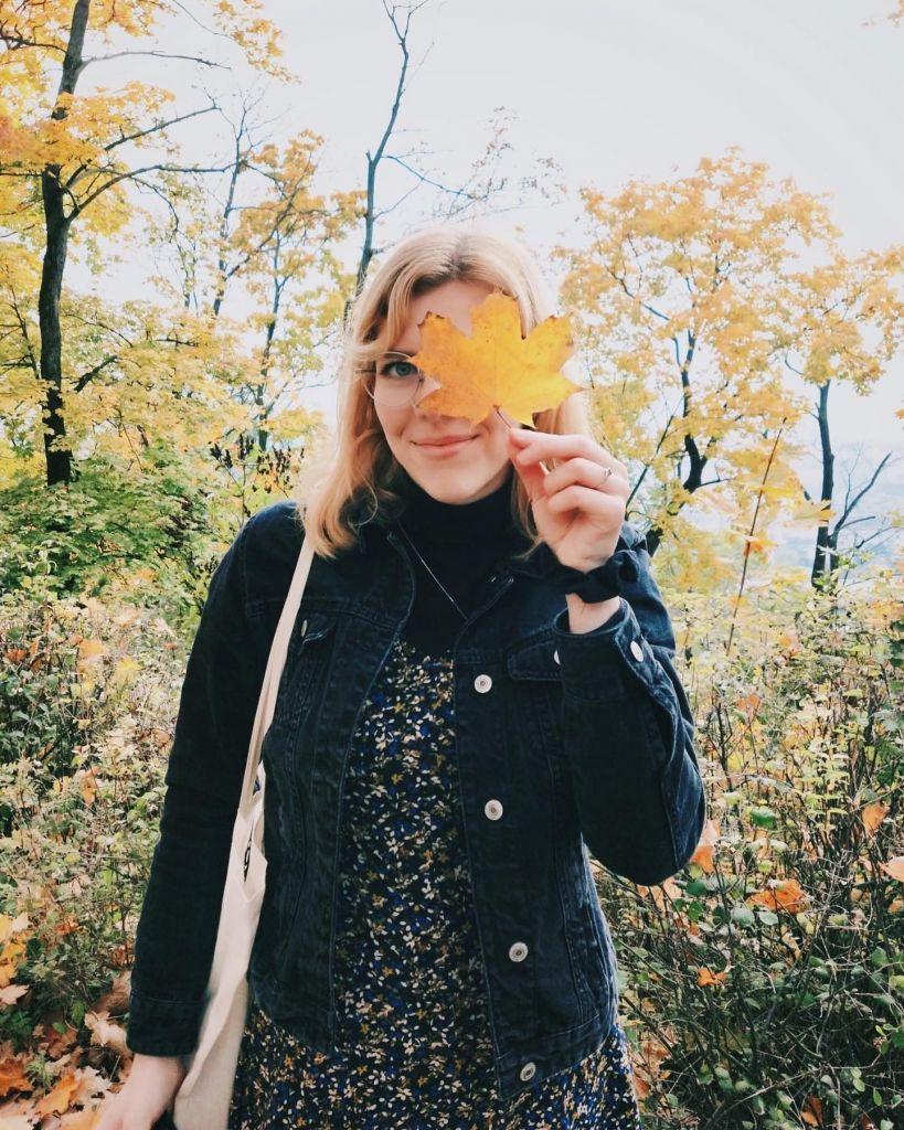 Portrait von einer Person, die ein gelbes Blatt vor ihr Gesicht hält