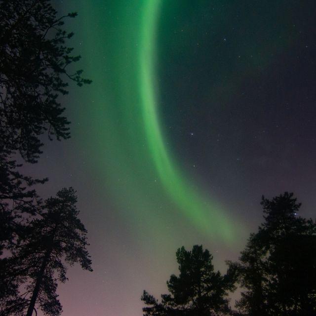 Ein geschwungenes grünes Nordlichtband zieht sich durch den Nachthimmel.
