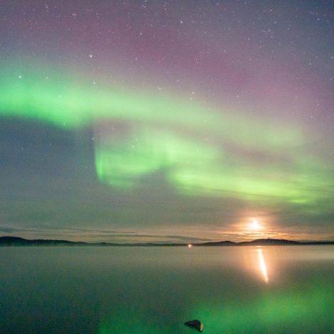 Ein grüner breiter Nordlichtschleier zieht sich über den Himmel und spiegelt sich im See