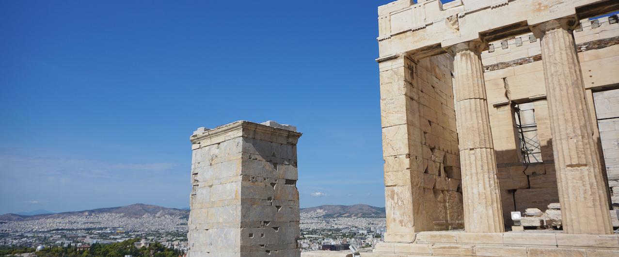 Auf der rechten Seite sieht man einen Teil der Akropolis und im Hintergrund Häuser und Bäume.