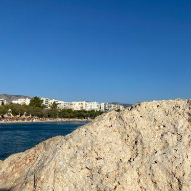 Auf der rechten Seite sieht man im Vordergrund einen Felsen, auf der linken Seite sieht man das Meer in Athen.