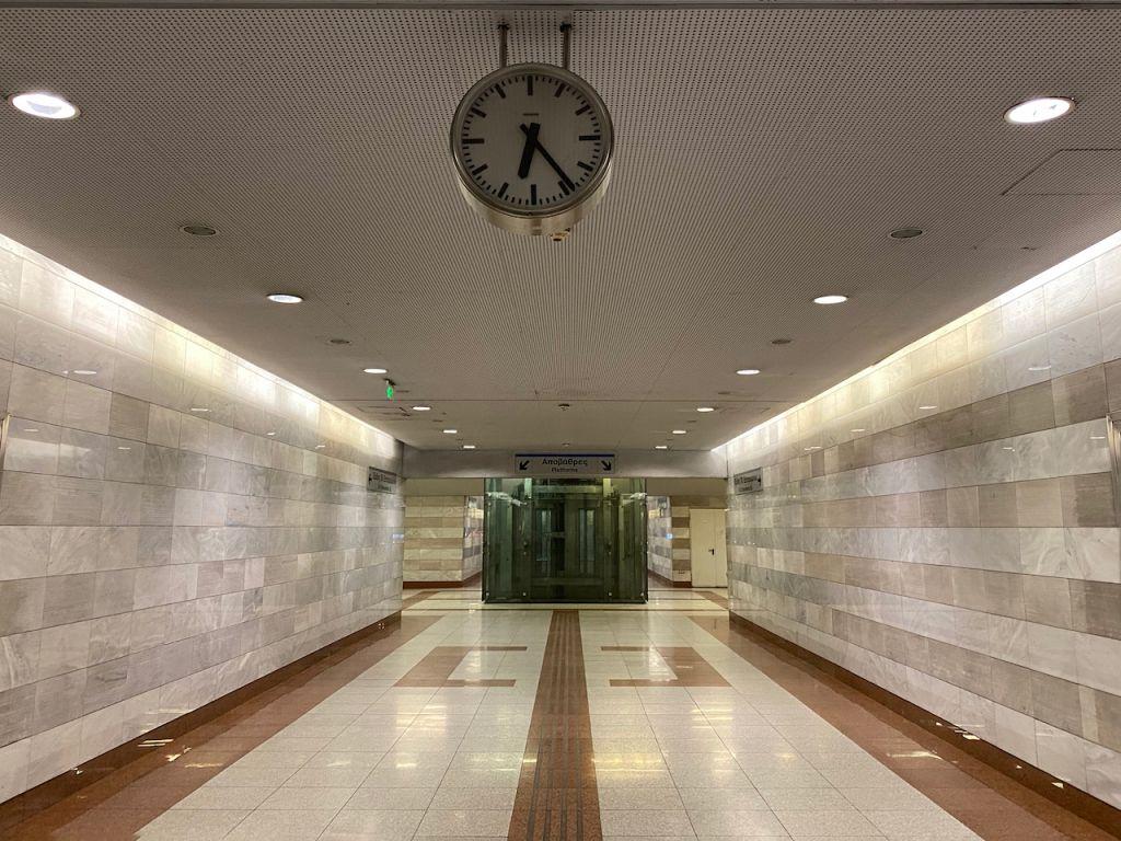Der Weg zur U-Bahn in Egaleo. Im Vordergrund hängt eine Uhr und im Hintergrund sieht man ein Schild, welches auf Treppen auf der linken Seite und Treppen auf der rechten Seite hinweist.
