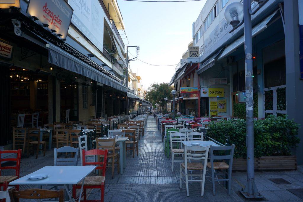 Einblick in eine Straße voll mit menschenleeren griechischen Restaurants. Die Stühle haben alle unterschiedliche Farben.