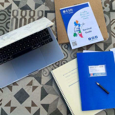 Man sieht einen gemusterten Tisch mit einem Laptop auf der linken Seite. Auf der rechten Seite liegen Hefte und ein Stift. Die Objekte wurden aus der Vogelperspektive fotografiert.