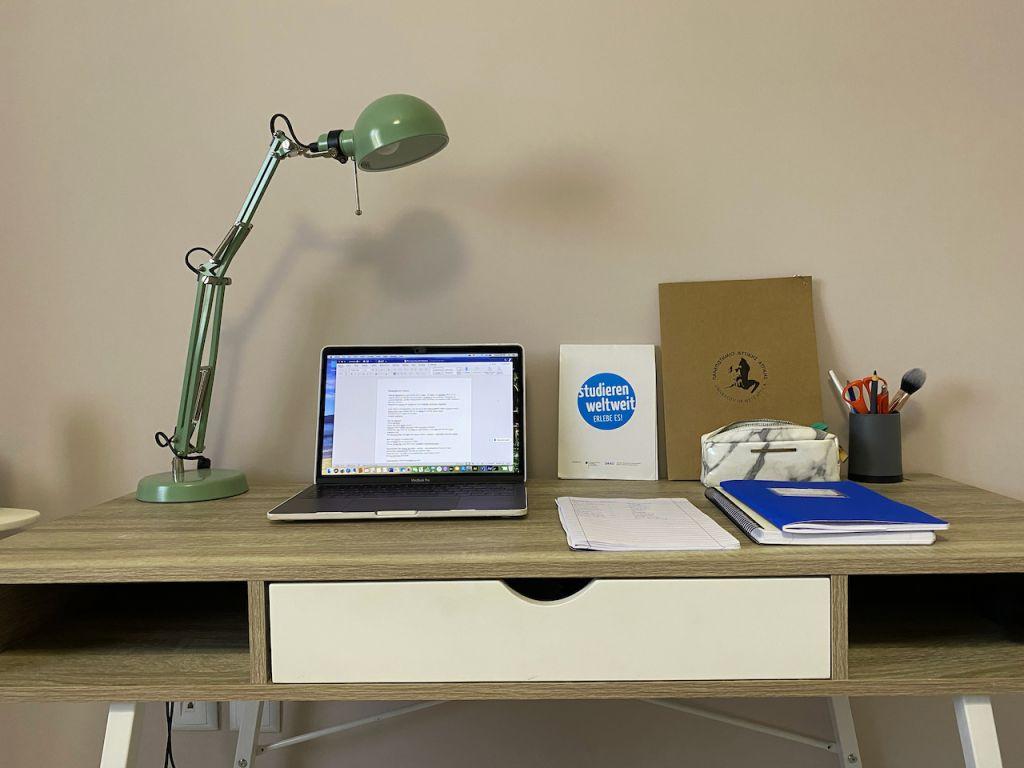 Ein Schreibtisch mit Laptop und grüner Tischlampe auf der linken Seite und Heften, Stiften und einer Federmappe auf der rechten Seite.