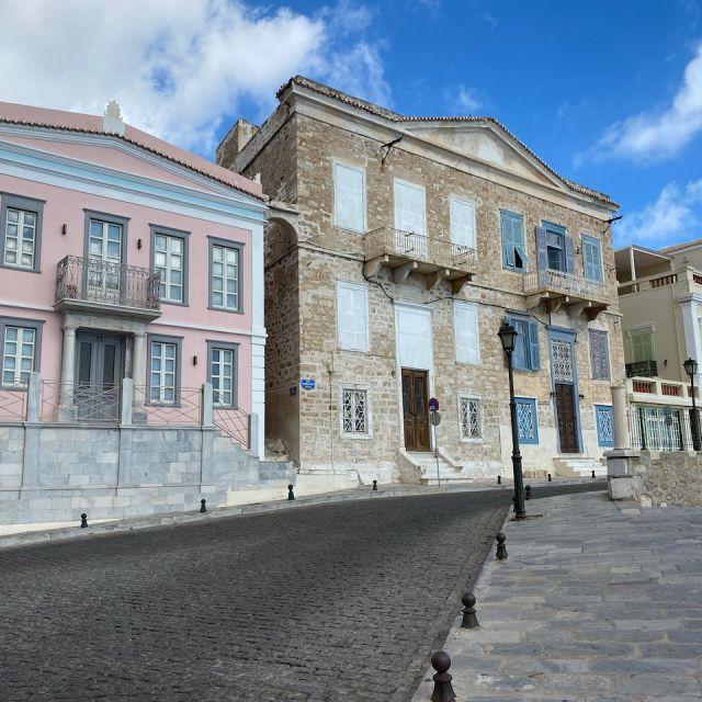 Altstadt von Syros. Auf der linken Hälfte befindet sich ein rosa Haus, in der Mitte ein braunes und auf der linken Seite ein Mintgrünes.
