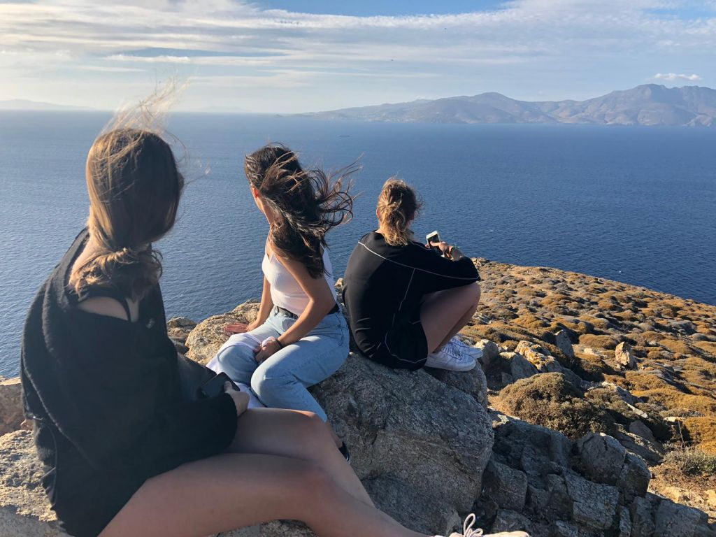 Drei Personen, die mit dem Rücken zur Kamera sitzen und aufs Meer blicken.