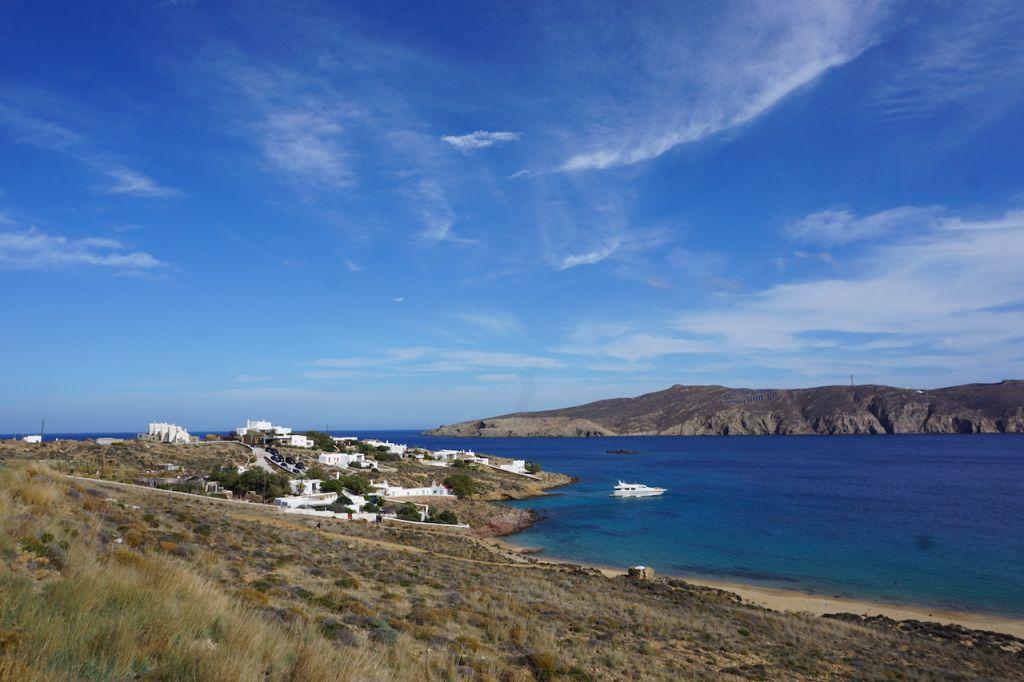 Auf der rechten Seite befindet sich das Meer und auf der linken Seite eine Wiese und der Strand. Im Hintergrund sind ein paar weiße Häuser zu sehen.