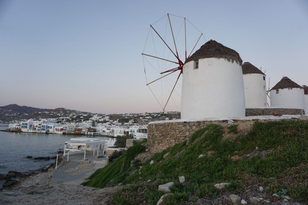 Auf der rechten Seite befinden sich vier große und weiße Windmühlen. Auf der linken Seite befindet sich das Meer und der Hafen von Mykonos.