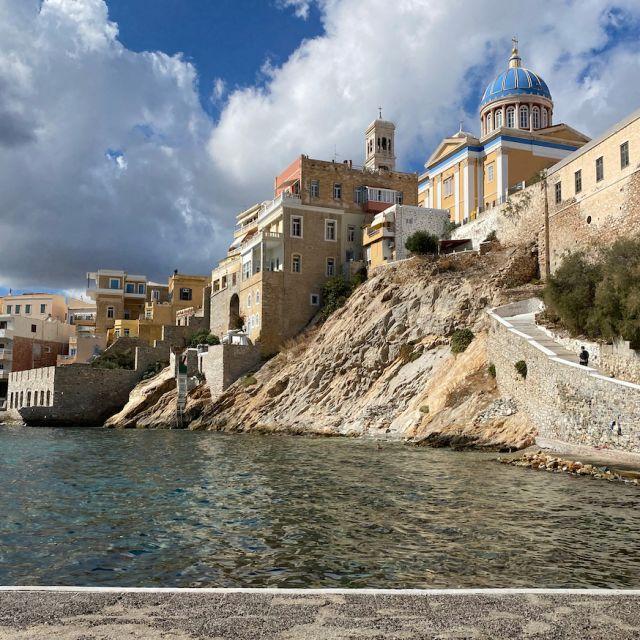 Der Blick von unten auf eine Kirche und die Stadt von Syros.