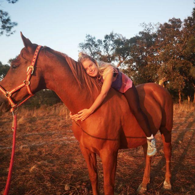 Frau auf einem Pferd beim Sonnenuntergang.
