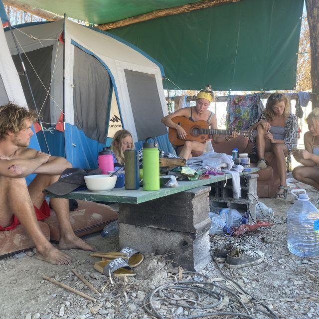 Menschen sitzen zusammen vor Zelten.
