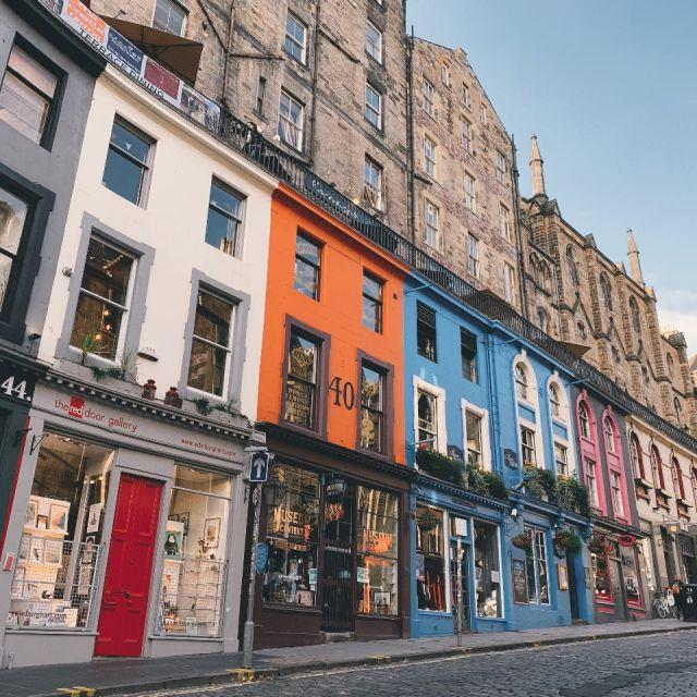 steile Straße in Edinburghs Altstadt, bunte Häuser mit vielen unterschiedlichen Geschäften im Erdgeschoss, darüber braune Steinhäuser