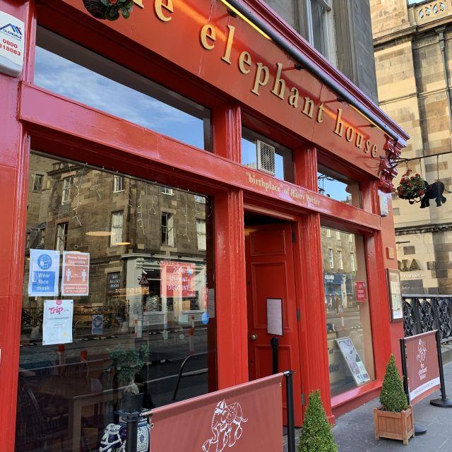 """Café, in dem J.K. Rowling ihre Bücher geschrieben hat, roter Hauseingang, große Fenster, goldener Titel """"The elephant House"""", grüne Pflanzen und Absperrungen"""
