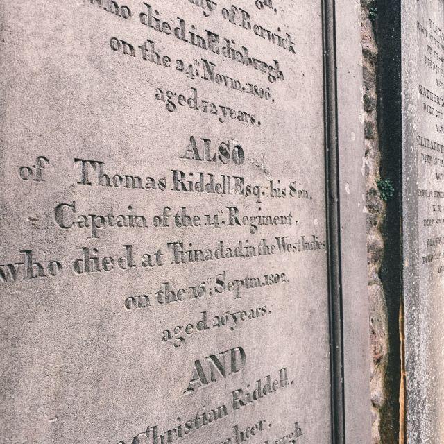 Grabstein mit Namen verstorbener Personen, zu lesen ist der Name Thomas Riddell, alter Friedhof in Edinburgh, die Namen dienten J.K. Rowling als Inspiration