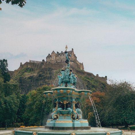 Park mit grünen Bäumen und großem Brunnen, Blick auf Burg, blauer Himmel