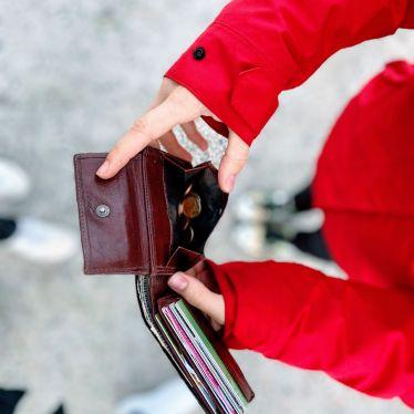 Jemand hält eine Portmonnaie mit etwas Kleingeld und vielen Karten in den Händen