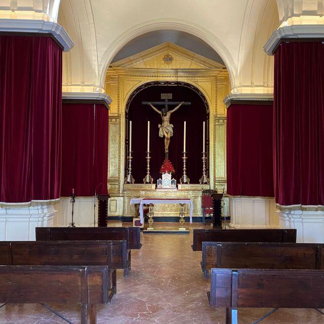 Sitzbänke recht und links, an der Stirnseite Jesus am Kreuz zwischen vier Kerzen.
