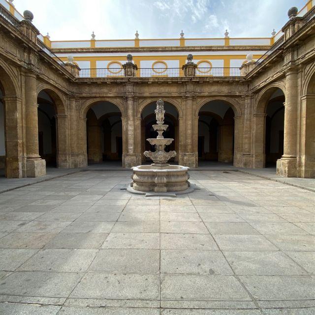 Innenhof mit steinernem Brunnen in der Mitte, außen Arkaden.