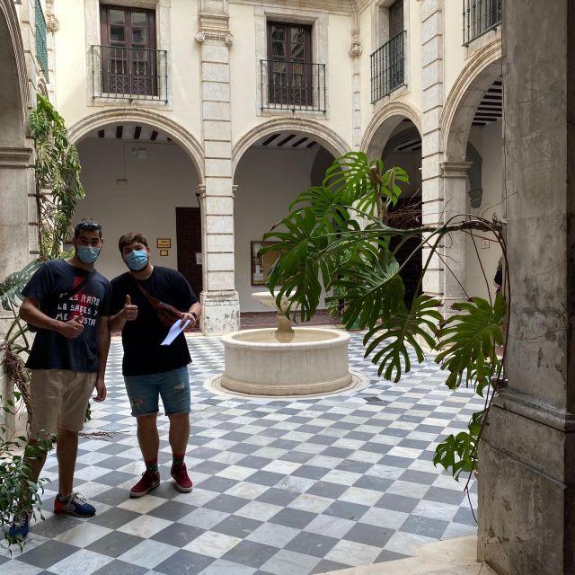 Innenhof mit Brunnen, blau-grau-gekachelter Boden und zwei Jungs mit Maske, die den Daumen ausstrecken.