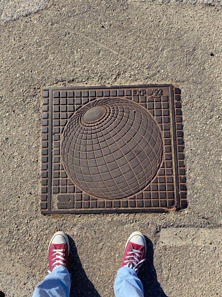 Quadratischer Gullideckel mit Weltkugel als Logo der Expo 92.