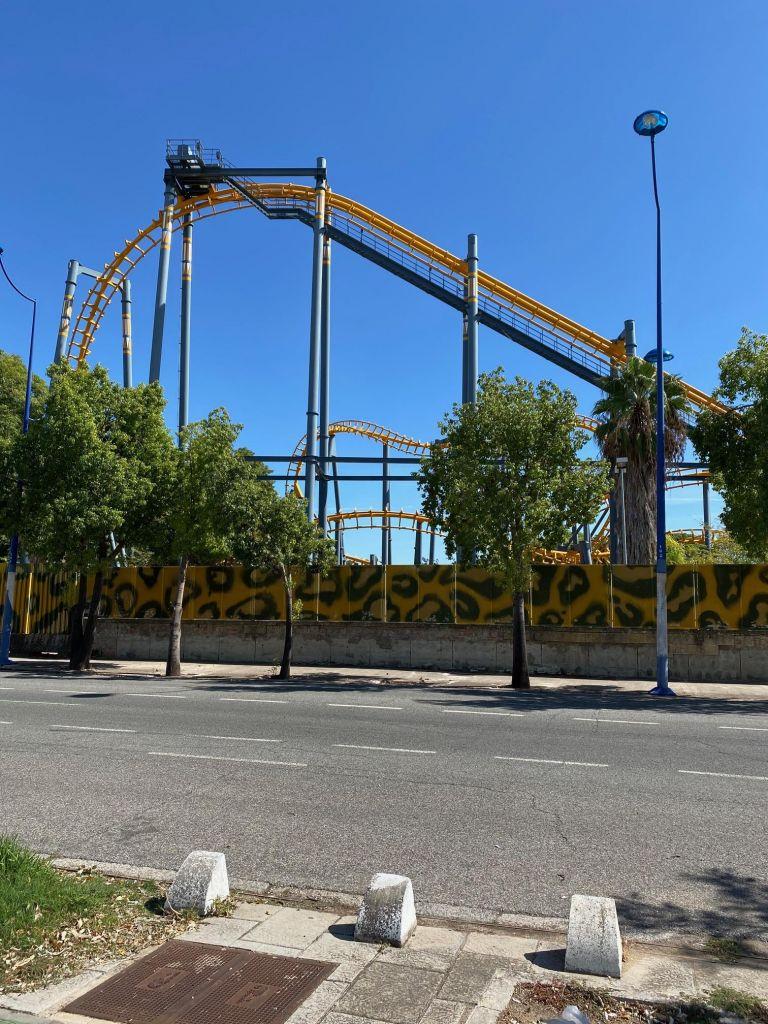 Gelbe Achterbahn ragt über Mauer hinaus.