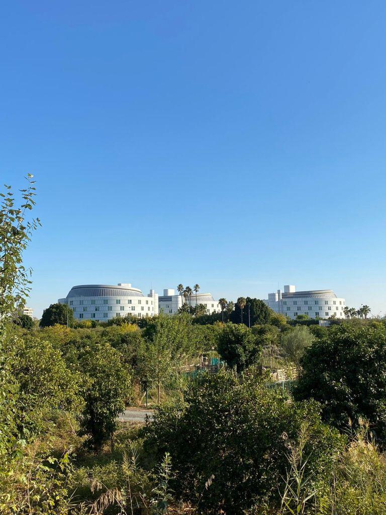Drei runde, weiße, futuristische Gebäude hinter einer Grünfläche.