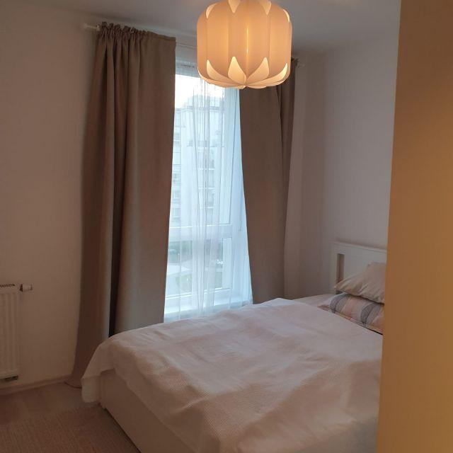 Mein Schlafzimmer mit bodentiefem Fenster, einem Doppelbett und einer dekorativen Lampe, die von der Decke hängt.
