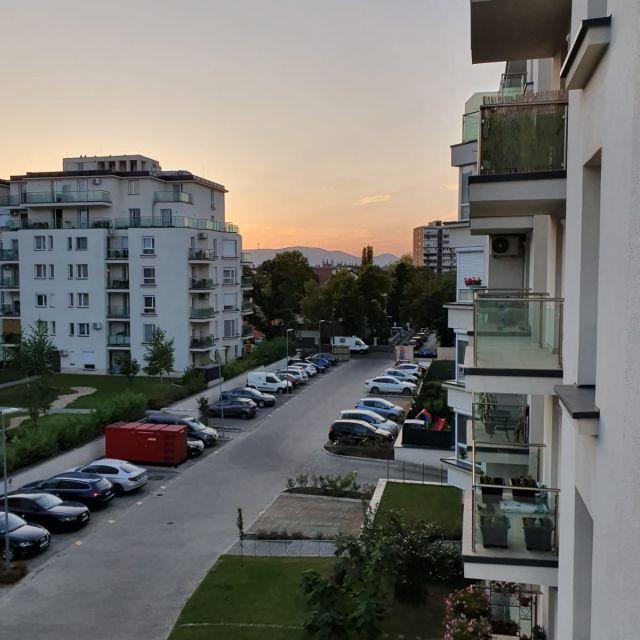 Der Ausblick von meinem Balkon mit Sonnenuntergang hinter dem Gebäudekomplex.
