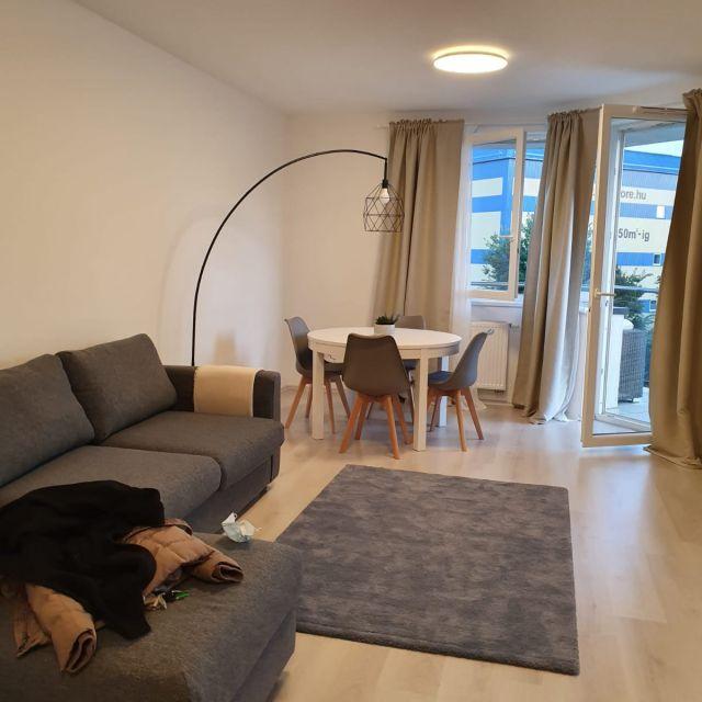 Mein Wohnzimmer mit Sofa, Esstisch und Zugang zum Balkon.