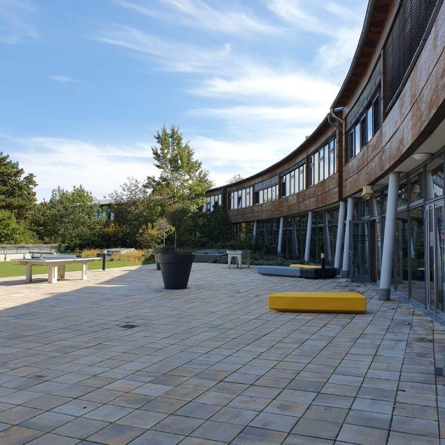 Das längliche Schulgebäude mit einem Teil des Schulhofes.