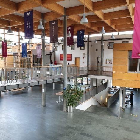 Der Eingangsbereich der Schule ist offen und hell mit Fensterfront, Treppen und Brücken.