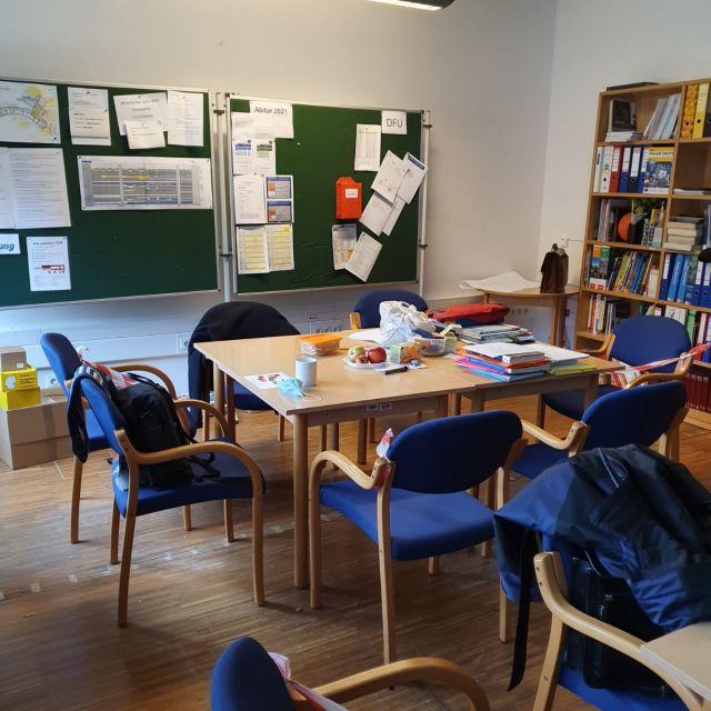 Eine Ecke des Lehrerzimmers mit Tischen, Stühlen und Pinnwänden.