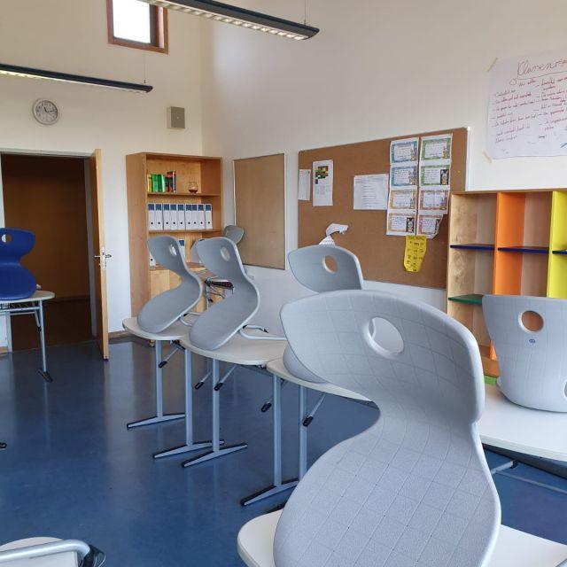 Ein Klassenraum mit Pinnwänden und hochgestellten Stühlen.