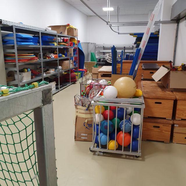 Der Geräteraum der Sporthalle mit vielen Sportgeräten wie Bällen und Schlägern.