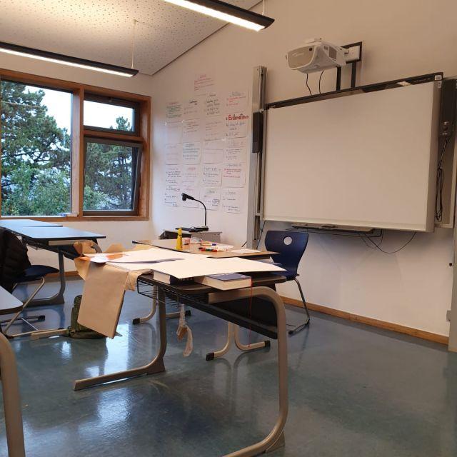 Ein Klassenraum mit Smartboard und Materialien auf dem Tisch.
